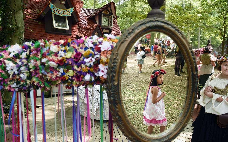 Xinyi Xie is reflected in a mirror as she walks by a booth selling garlands at the Maryland Renaissance Festival in 2015.