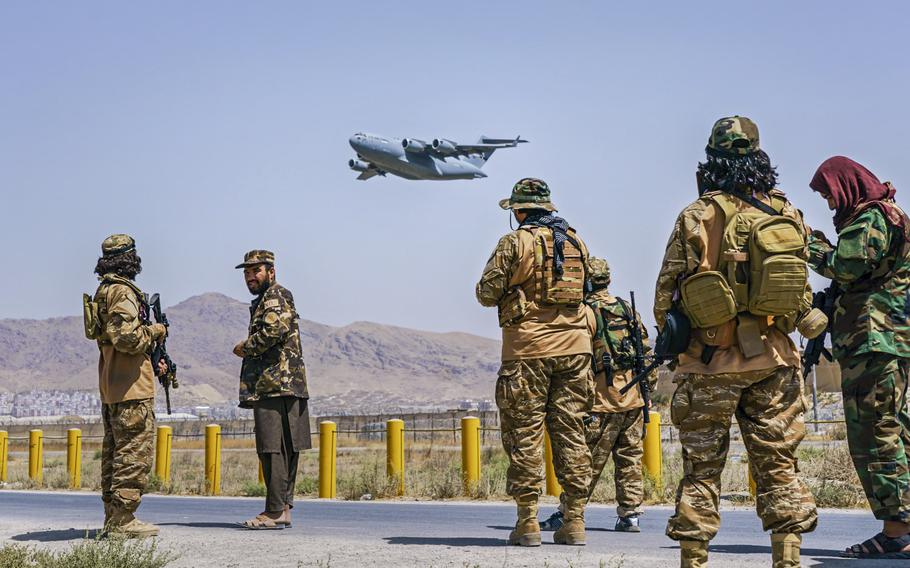 A C-17 Globemaster takes off as Taliban fighters secure the outer perimeter, alongside the American controlled side of of the Hamid Karzai International Airport in Kabul, Afghanistan, on Aug. 29, 2021.