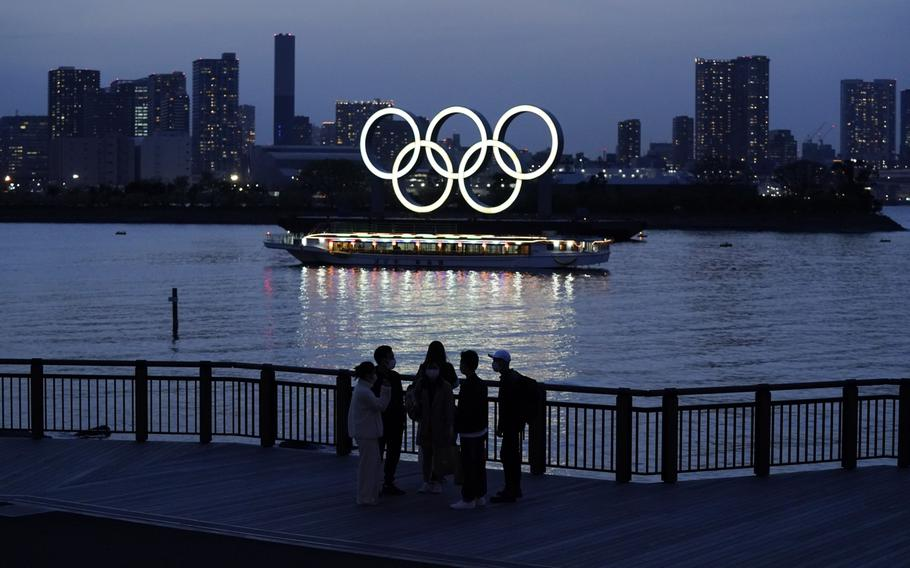 People watch illuminated Olympic rings floating in the waters off Odaiba island in Tokyo on April 1, 2021.