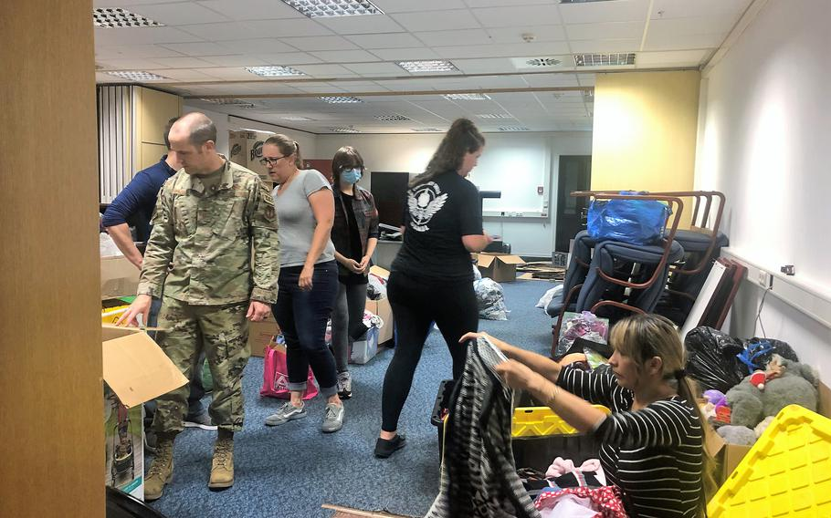 Andrew Wilder, an Air Force first sergeant, front left, and half a dozen volunteers from the Kaiserslautern military community sort through donated goods at Ramstein Air Base, Germany, August 19, 2021. Donations were made been collected for evacuees from Afghanistan, who were expected to arrive at the base.