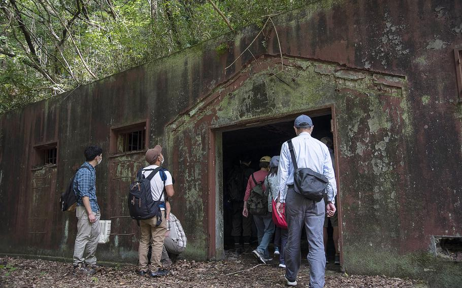 Japanese visitors tour a World War II-era munitions storage site at Tama Hills Recreation Area in western Tokyo, Wednesday, May 26, 2021.
