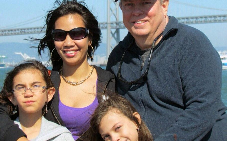 Paul Alexander (right), his wife Lou, and daughters Caitlin (with glasses) and Taryn (smiling) pose in front of the Bay Bridge in San Francisco, Calif., on a recent trip that made use of space-available flights.