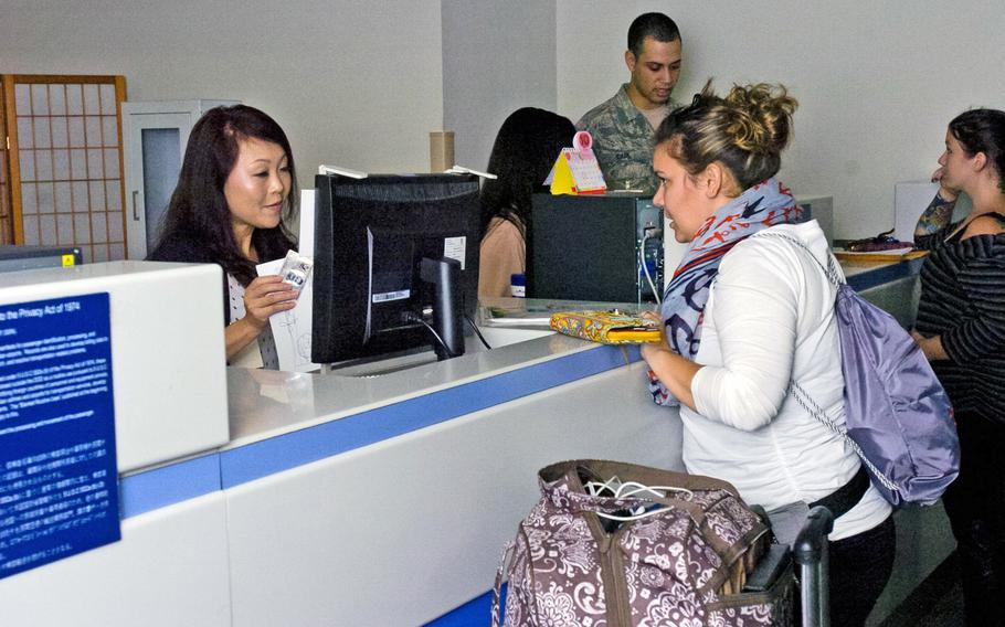 Kimberly Bowens, a wife from Naval Air Facility Atsugi, Japan, checks in at a ticketing counter prior to boarding a flight at Yokota Air Base, Japan, Sept. 26, 2013.