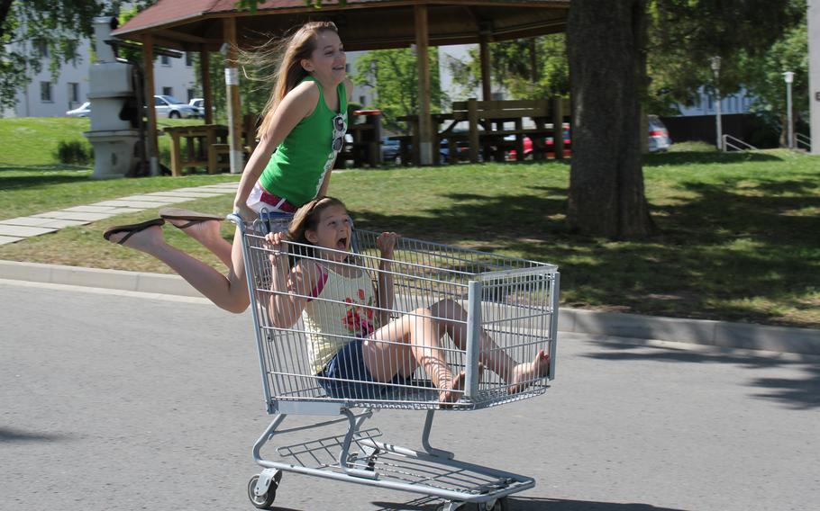 Lisa Smith Molinari's daughters, Anna and Lilly, ride on an abandoned shopping cart when the family was stationed at Patch Barracks in Stuttgart, Germany, in the summer of 2010.