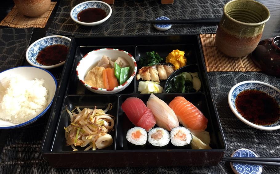A lunch bento box from pre-pandemic times at Hashimoto in Saarbruecken, Germany. The meal includes sushi, grilled fish, vegetables, pickles, rice and green tea.