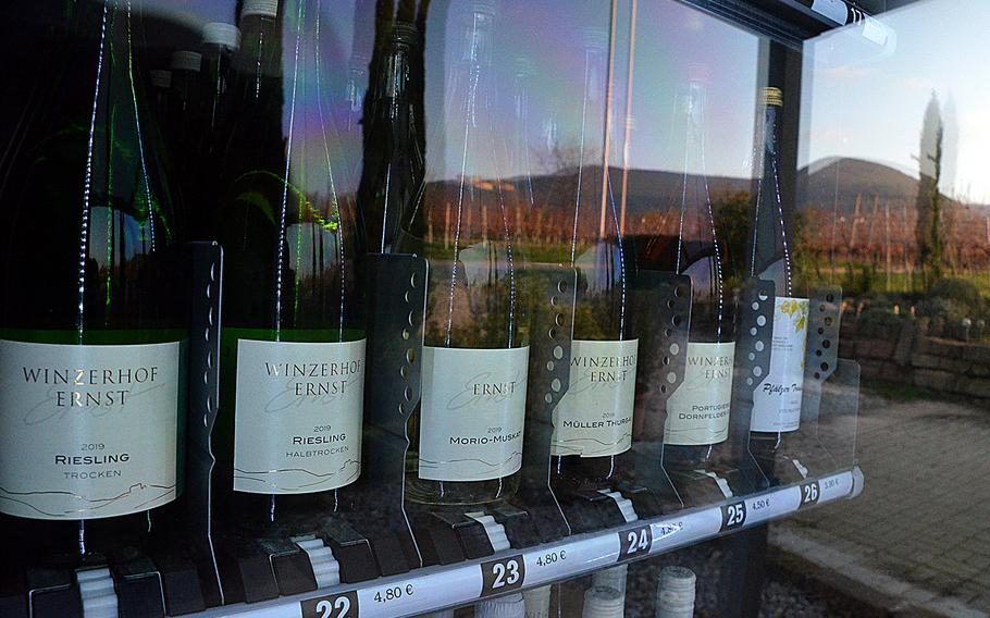 Vineyards and an ancient cloister are reflected in the glass of the wine vending machine at Winzerhof Ernst in Maikammer, Germany, on Nov. 30, 2020. The vending machine sells a selection of reds, whites and roses, along with grape juice, water and glasses to drink them from.