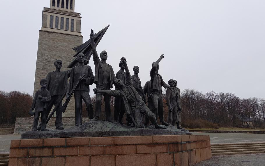 """The Bell Tower is part of the memorial the East German government built at the Buchenwald site. In front of it, a bronze statue by Fritz Cremer, called """"Revolt of the Prisoners,"""" has become one of the focal points of the site."""