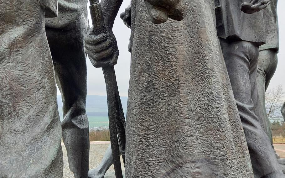 """One of the 11 figures depicted in """"Revolt of the Prisoners,"""" a statue by sculptor Fritz Cremer that stands in front of the bell tower at the Buchenwald memorial site, defiantly clenches his fist."""