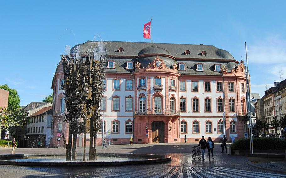The Fastnachtsbrunnen fountain on Schillerplatz square in Mainz, Germany, is covered with historic buildings and people, including symbols of carnival.