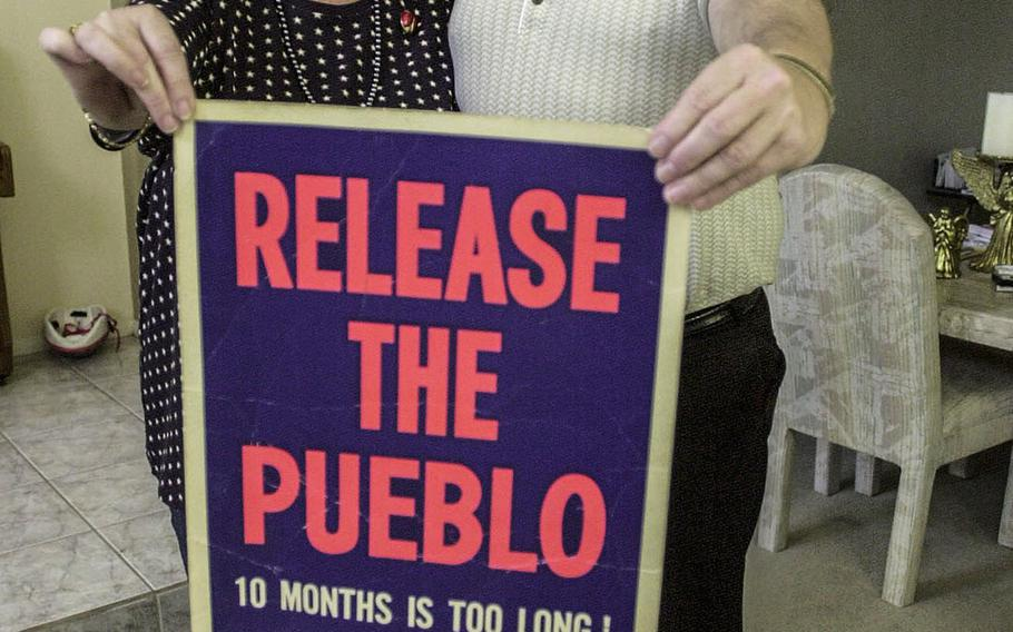 In a February, 2000 photo, Pueblo survivor James Kell and his wife, Pat, hold up a sign from 1968.
