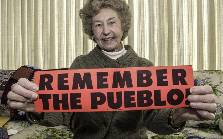 In a February, 2000 photo, Rose Bucher holds up a bumper sticker that she circulated in 1968 in a effort to focus attention on the release of the Pueblo crew.