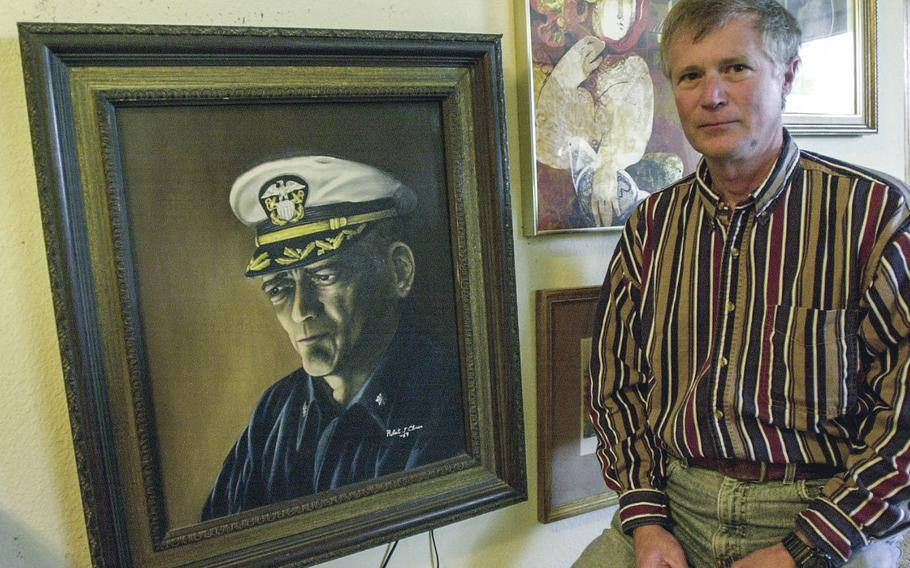 """In a February, 2000 photo, Robert J. Chicca stands next to a portrait of his former Commander, Lloyd """"Pete"""" Bucher, that he painted himself."""