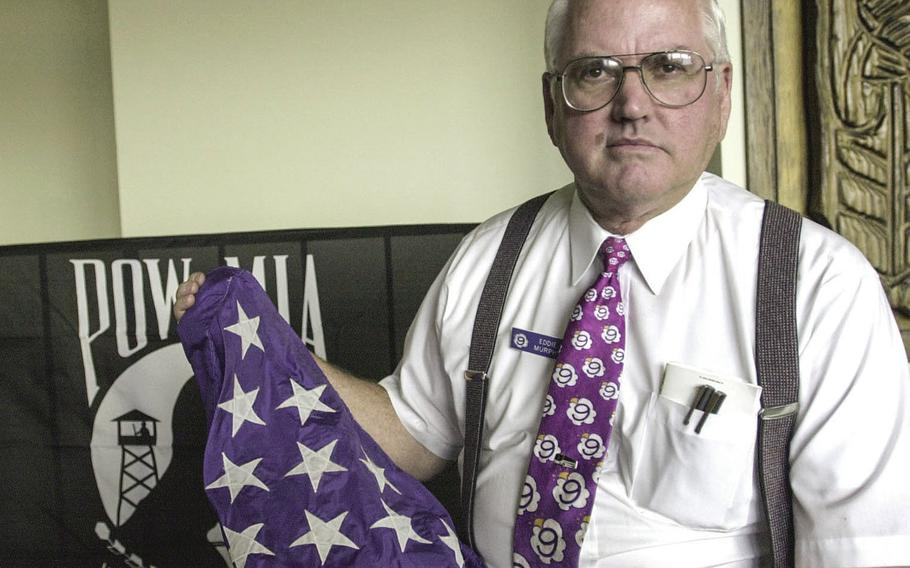In a February, 2000 photo, Edward R. Murphy Jr., the ship's executive officer, displays his American flag that was flown over the USS Pueblo before it left on its final voyage.