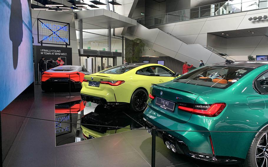 The main floor of the BMW Welt in Munich, Germany, Oct. 14, 2020, includes, the latest models of the BMW M4, center, and M3, right.
