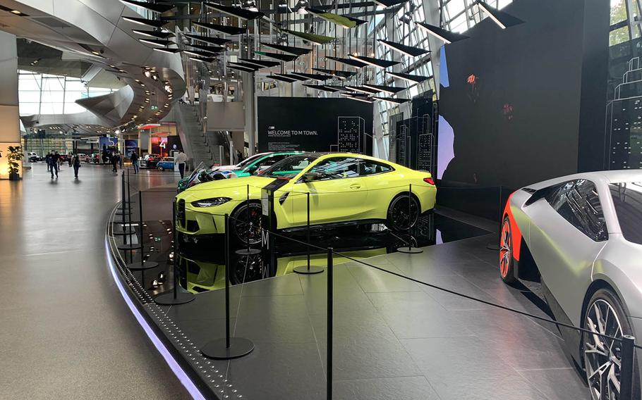 A yellow BMW M4 sits on display beside a prototype of the BMW Vision M Next electric sports car on the main floor of the BMW Welt in Munich, Germany. The museum features new cars BMW is slated to release to the public. The BMW Welt is scheduled to be closed until at least March 7 because of coronavirus prevention measures.