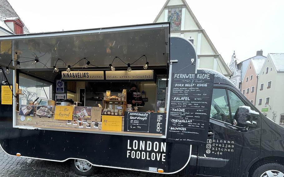 Nina & Velja's Kitchen food truck offers ''wanderlust cooking,'' including brownies, quesadillas and slow-cooked pork belly with kimchi, onion jam, hummus, aioli and salad, at the outdoor market in Weiden, Germany, April 7, 2021.