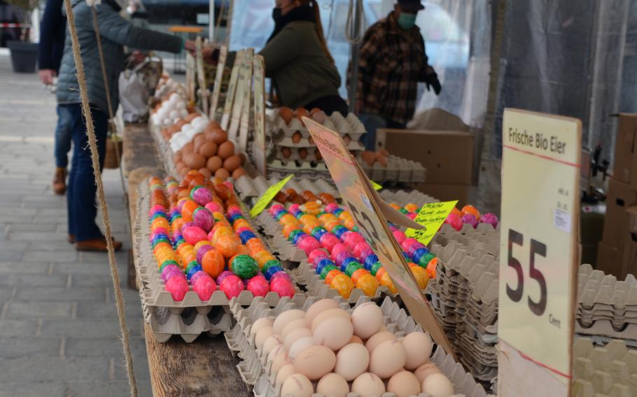 A woman pays for eggs at a stand in the outdoor market in Kaiserslautern, Germany, on Tues., April 6, 2021. The colorful eggs in the foreground are hard-boiled eggs from free-range chickens fed only organic foods.