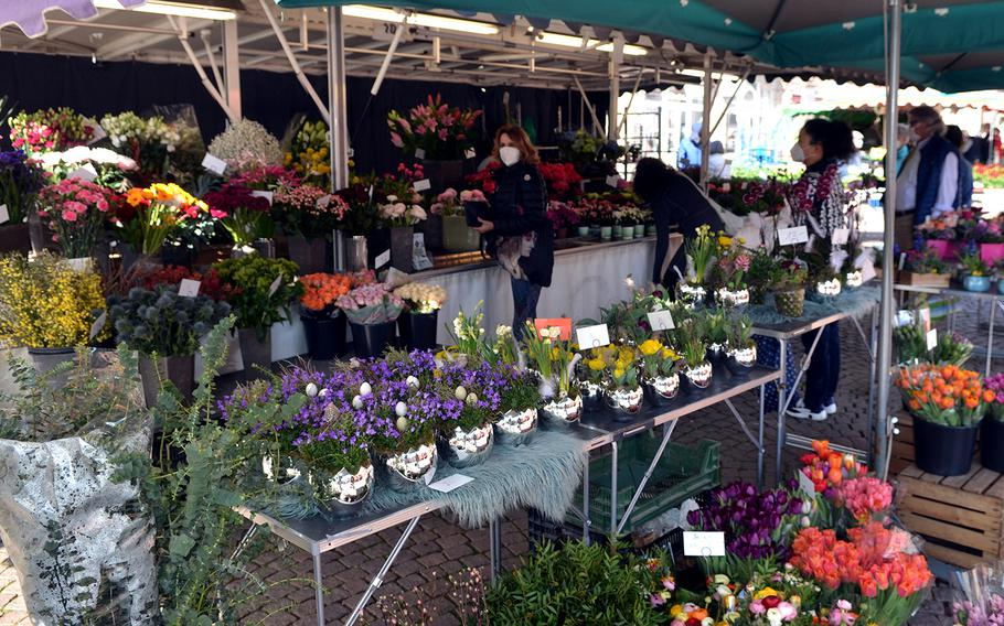 People stand back from each other to respect the coronavirus rules at a flower stand at Wiesbaden's farmers' market on March 3, 2021.