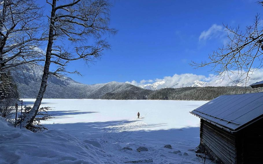 A person walks across the frozen Eibsee in Grainau, Germany on March 6, 2021. The lake nearby the Zugspitze, Germany's tallest mountain, has a gentle hiking trail surrounding it.
