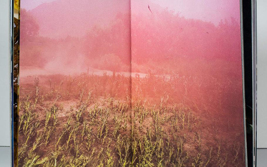 """Smoke obscures a field in """"Attention Servicemember,"""" by U.S. Army war veteran Ben Brody, a book that attempts to convey the experience of the Iraq and Afghanistan Wars via photography."""
