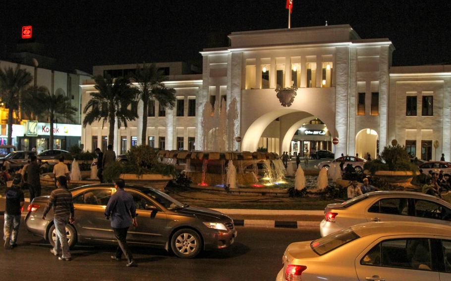 The Bab al-Bahrain (Gateway of Bahrain) in central Manama, Bahrain, is a grand historical building with a bubbling fountain before it and an arch marking the entrance to the Manama Souq.