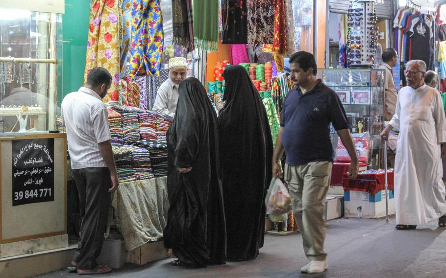 Colorful fabrics tempt two women at one of the shops in the Manama Souq in Manama, Bahrain, on  Sept. 16.