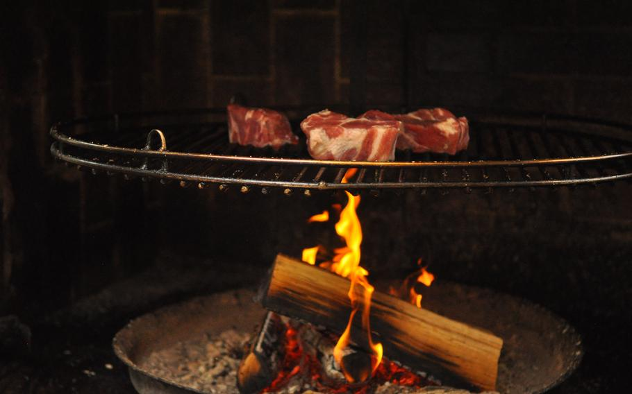 """Cuts of beef roast on an open flame outdoors at a cafe in Idar-Oberstein, Germany. The town is known for its """"Spiessbraten,"""" a specialty brought back by gem cutters from South America."""