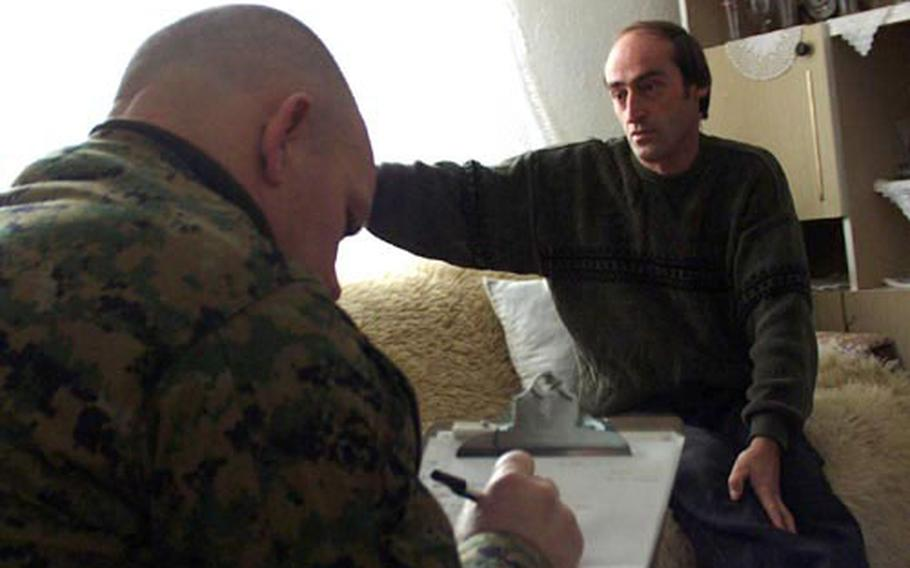 Marine Maj. John Church Jr., left, takes notes as Sabit Shrnu, an Albanian, is interviewed in his home by another Marine. Church is part of the 415th Civil Affairs Battalion at Camp Bondsteel and on Tuesday they talked with Shrnu, a village leader about his living conditions and what help his community needs.