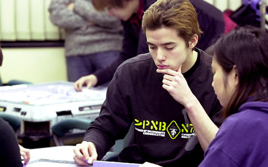 John O'Connor concentrates on a game of mah-jongg. O'Connor is a Nile C. Kinnick High School graduate and the son of a former Marine.