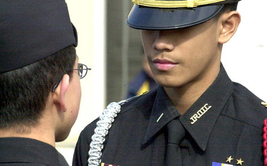 Ervin Mercado performs a personnel inspection a junior cadet on the Kinnick High School courtyard.