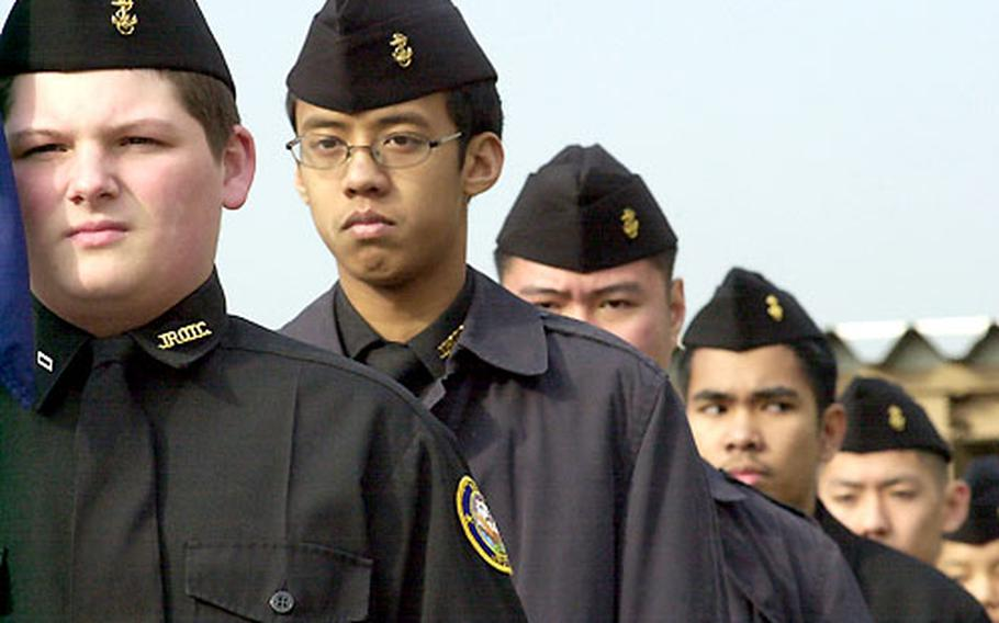 JROTC Cadet Christopher Woody is the guidon carrier during marching drills in the Kinnick High School courtyard.