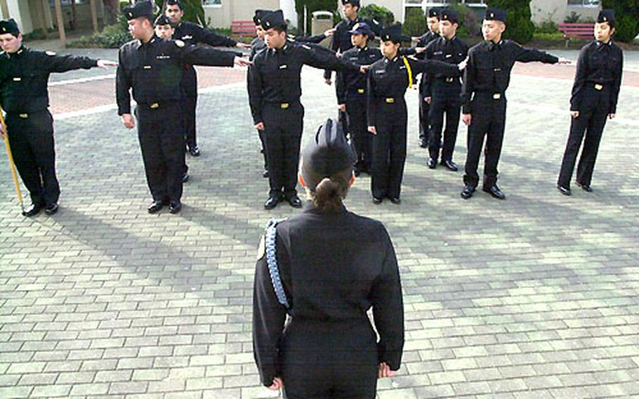 JROTC Cadet Jacqueliyn Guerrero gives the command to dress right to prepare the Kinnick High School JROTC unit for personnel inspection.