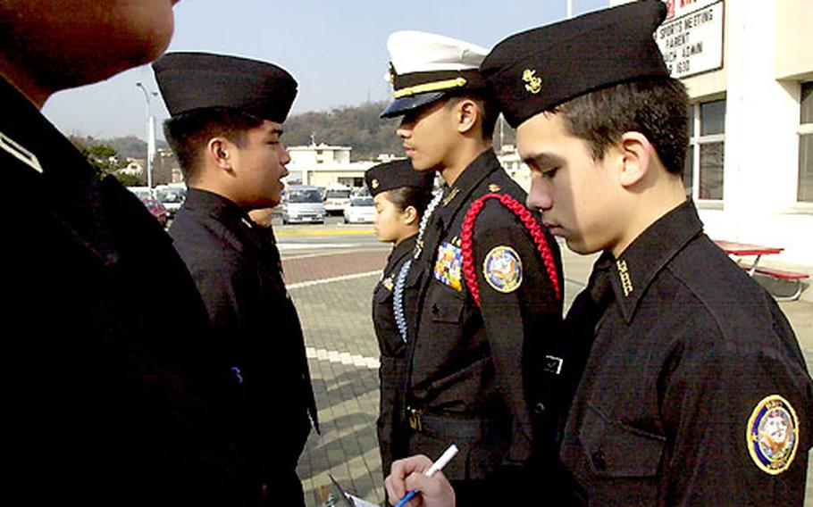 JROTC Cadet Eddie Calvert is the yeoman writing down discrepancies while Ervin Mercado performs a personnel inspection.