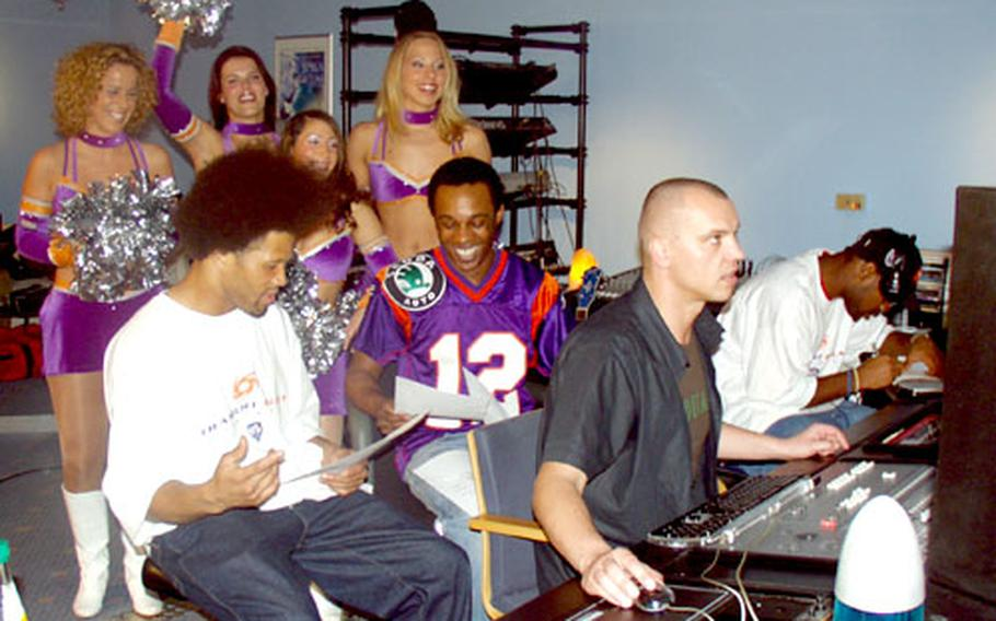 """Frankfurt Galaxy cheerleaders Cindy, Jenny S., Sibel, and Anne listen to """"Here We Come,"""" as A.K.-S.W.I.F.T., center, ensures everything is flowing. Also pictured are, at far left, Chris Pointer, and at far right, Calvin Spears, Galaxy players; and Paul Schulte, a producer."""