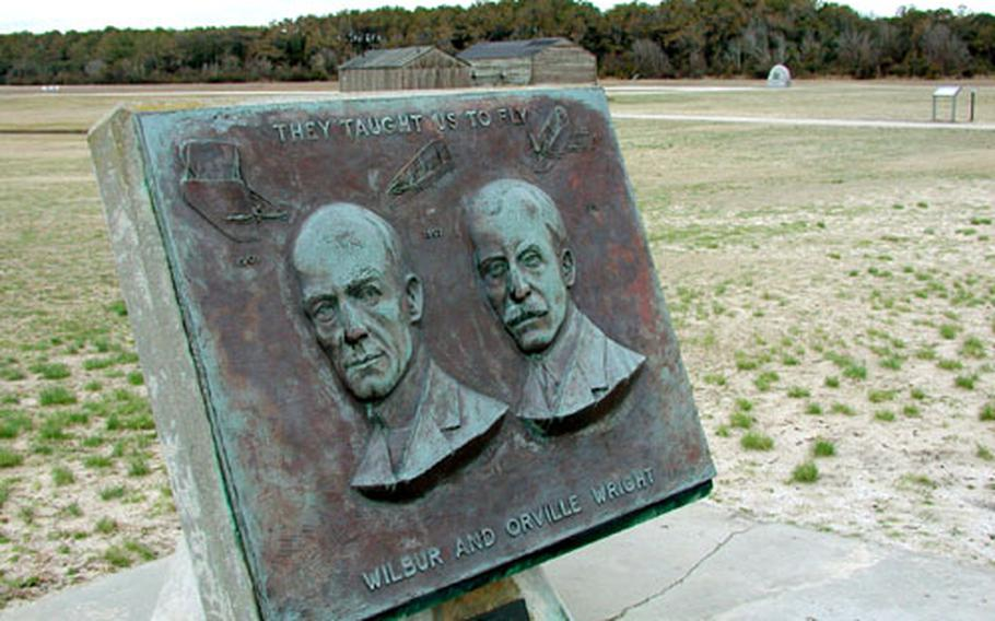 A plaque honoring the Wright brothers at Kill Devil Hills. In the background is the field where Orville made the first airplane flight 100 years ago; the buildings are recreations of the sheds where the brothers lived and stored their plane.