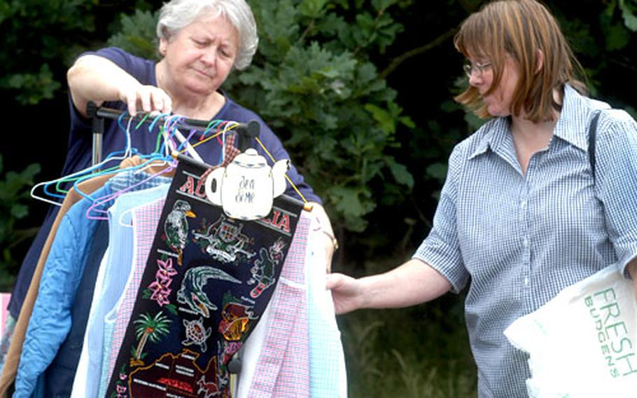 Clothes get a going-over at a car boot sale in Beck Row, home of RAF Mildenhall, England. A church sponsored the sale as a way of fostering community relations.