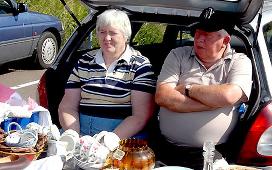 Two sellers sit in their car boot while displaying their wares at a car boot sale in Cambridge, England.