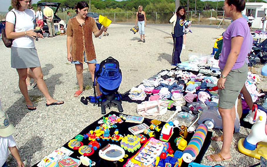 A customer bargains with Laura Skinner over a baby backpack during the monthly flea market at the Naval Station Rota, Spain, drive-in.