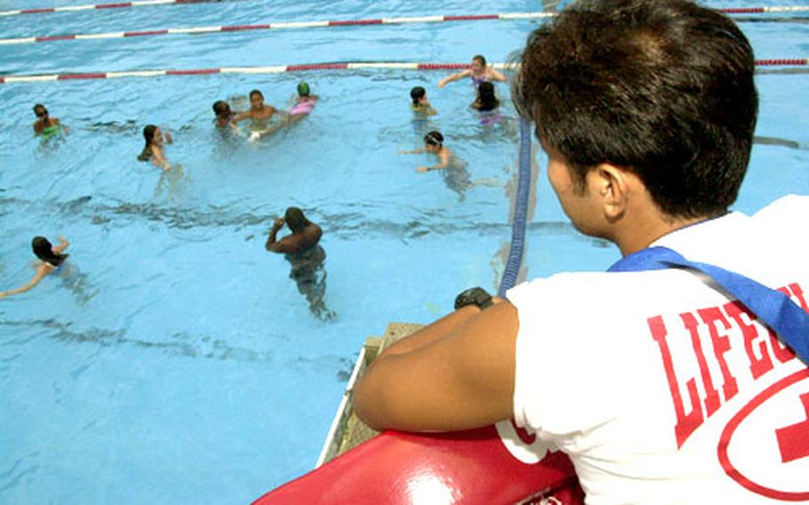 People who work outdoors, including lifeguard Kanazuka Takeshi at the Yokosuka Naval Base pool, need to be vigilant in applying SPF 30 sunscreen to avoid skin damage that could lead to skin cancer. The children might have entered the pool wearing sunscreen, but they'll need to reapply after toweling off.