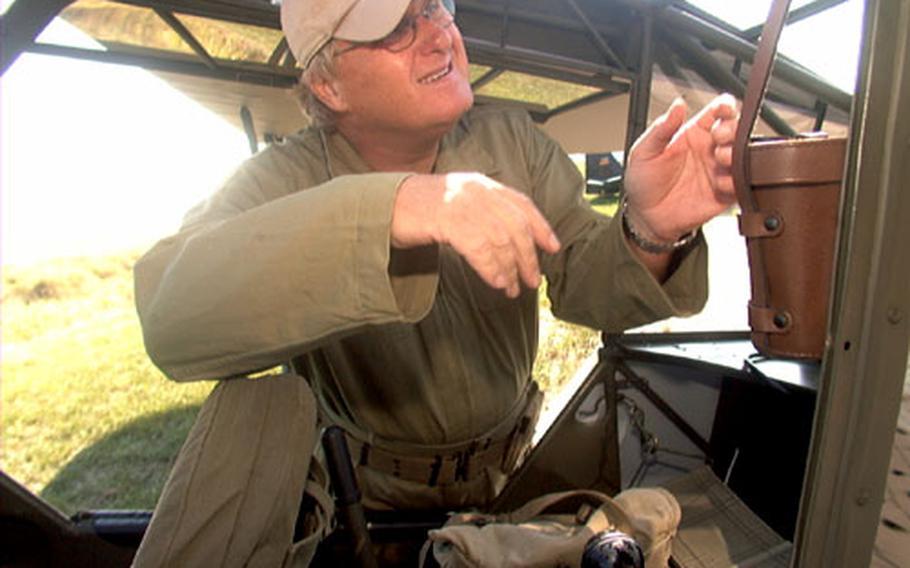 Whelan conducts a final pre-flight check of his Piper L-4B airplane.