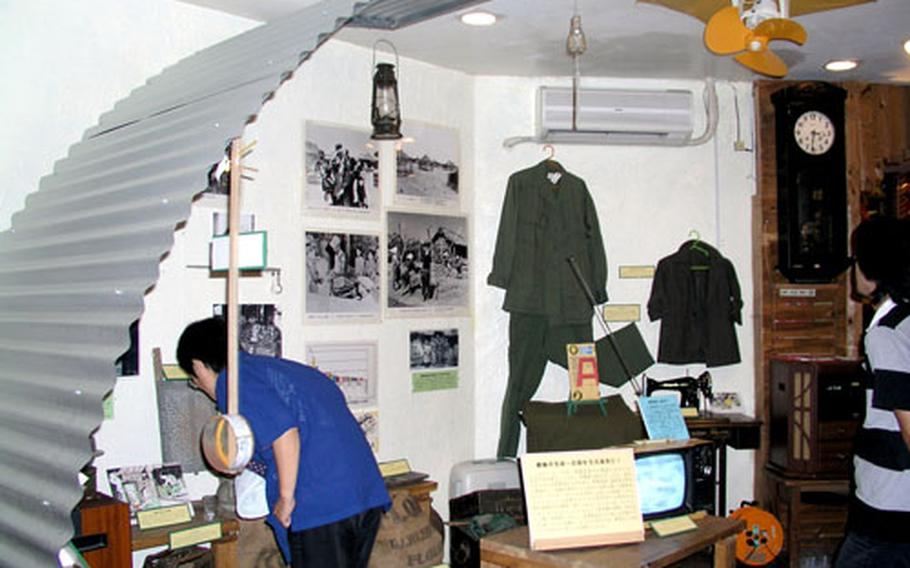 A visitor examines items displayed in a recreated room inside a Quonset hut at Histreet, a museum near Kadena Air Bases's Gate 2. The museum recreates the life of people who lived in Okinawa City, then called Koza, after World War II.
