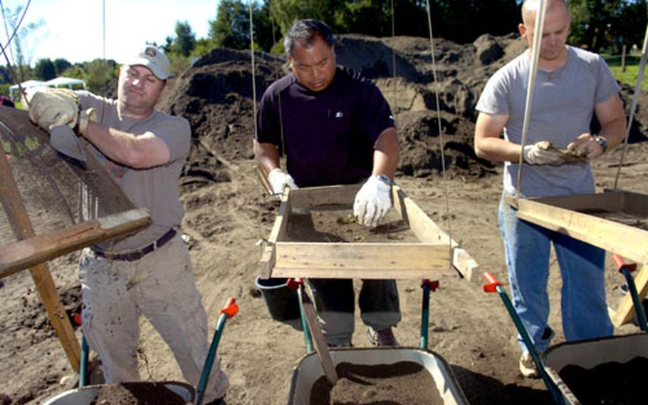 Members of the Joint POW/MIA Accounting Command recovery team — from left, Air Force Master Sgts. David Metherell and Rodney Acasio, and Army Sgt. Jimmy Phillips — screen dirt at the site.