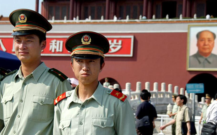 Two Chinese soldiers pose for pictures with their friends in front of the Gate of Heavenly Peace outside the Forbidden City.