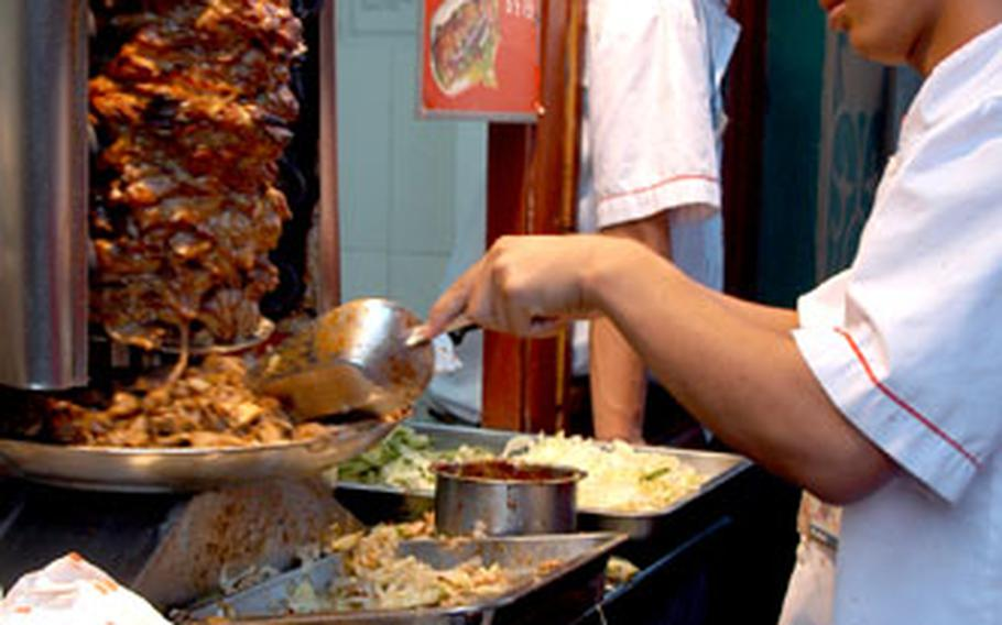 Turkey is sliced from a rotisserie then stuffed into a pocket bread at the outdoor food court at Wangfujing Daije shopping area.