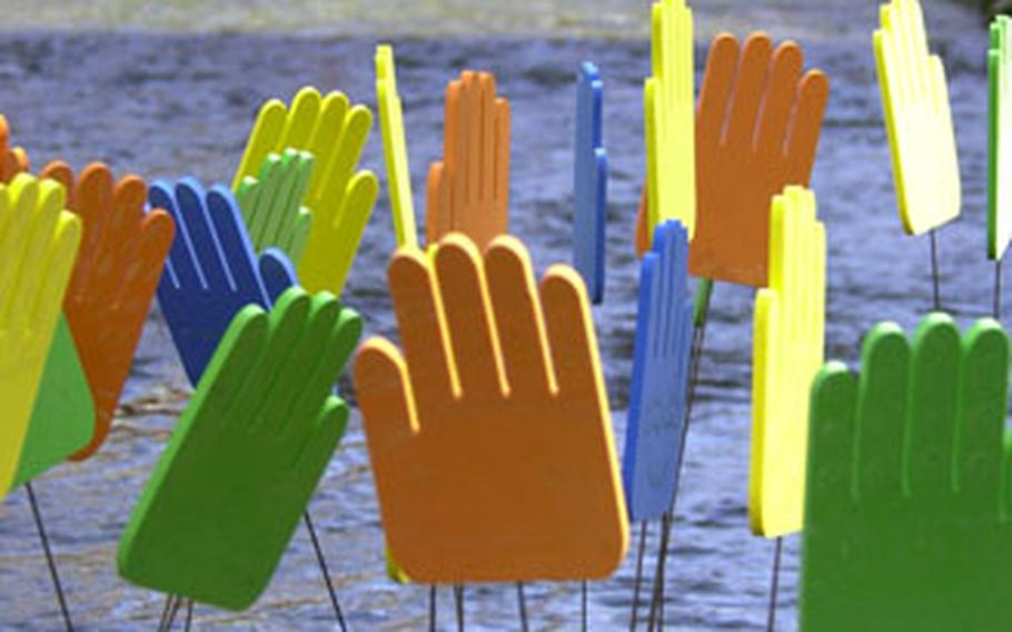 A collection of brightly colored hands, an art project, stands in the center of the Cheonggye Stream in downtown Seoul.