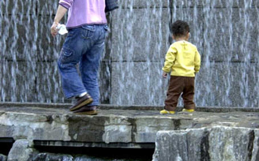 A woman and toddler make their way across a narrow bridge, with a waterfall on one side and the Cheonggye Stream on the other.