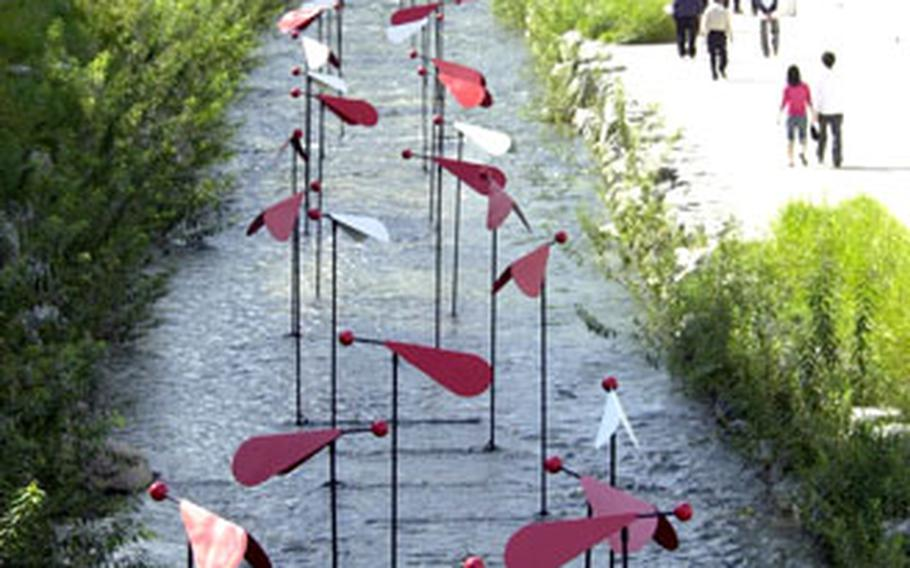A series of red and white artwork stands in the center of Cheonggye Stream.