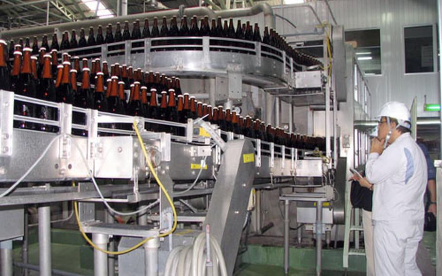 Tour guide Noriyuki Kise explains the bottling process at Orion Brewery in Nago, Okinawa.