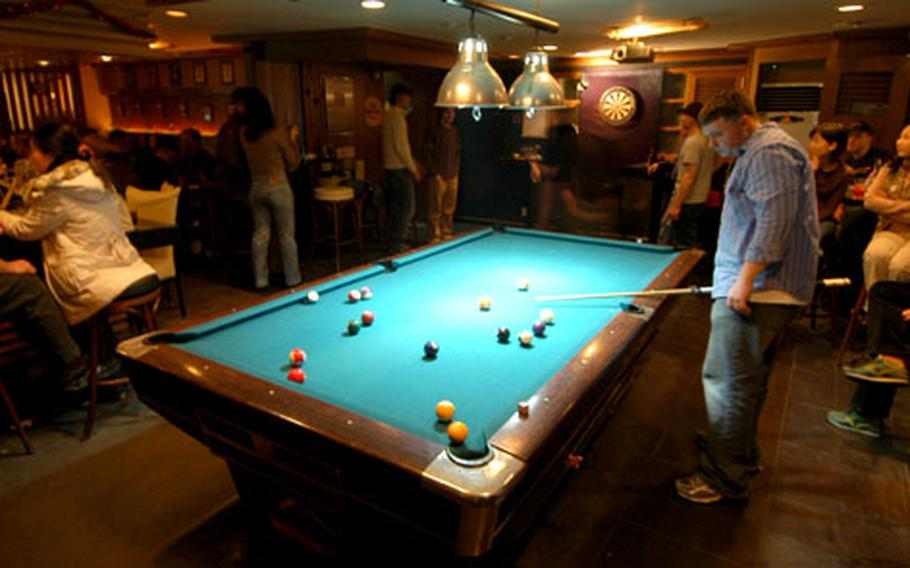 """Customers play pool and darts at Jester's, a local """"everyone's welcome"""" watering hole in Itaewon, South Korea."""