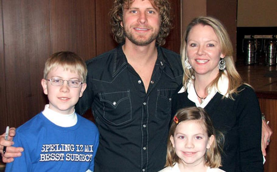 Dierks Bentley poses with long-time fan Carla Foster and her children, Megan, 8, and Zachary, 12 after a recent concert in Baumholder, Germany.